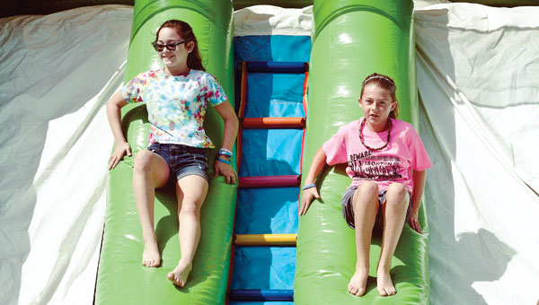 Arianna Schaus, left, and Shaelyn Myers, right, make their way up the inflatable slide backward on Saturday while attending the Kids Fun Day in Hanging Rock.