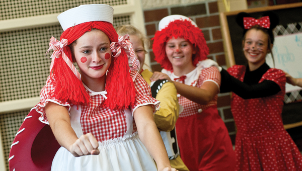 Raggedy Ann, played by Hannah Keating, leads the conga line during the Irontom High School flag corps and majorette team fundraiser Saturday in the school's cafeteria.