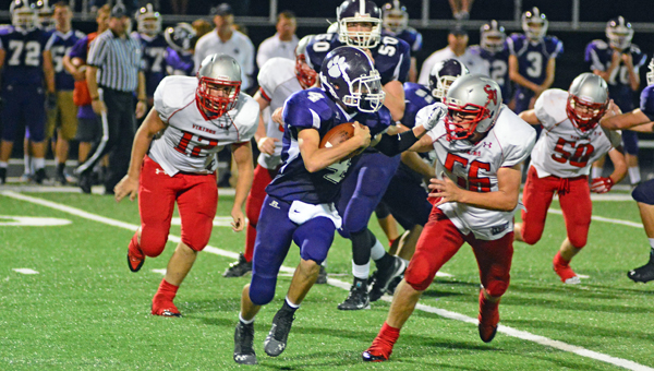 Chesapeake Panthers' quarterback Casey McComas (4) tries to outrun Symmes Valley defenders Travis Gates (56) and Jarod Sheppard (12) during Friday's game. McComas led the Panthers to a come-from-behind 21-18 win in the closing seconds. (Kent Sanborn of Southern Ohio Sports Photos)