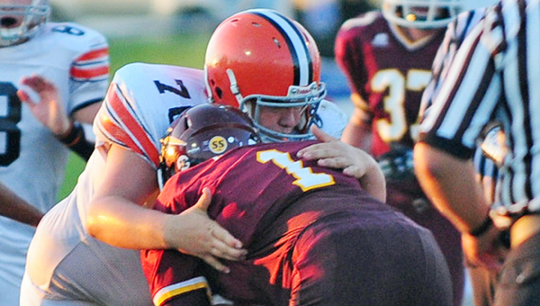 Ironton defensive lineman Hayden Robinson (76) wraps up Russell's Evan Ison for a mere 1-yard gain during Friday's game. The Fighting Tigers whipped Russell 36-9. (Tony Shotsky of Southern Ohio Sports Photos)