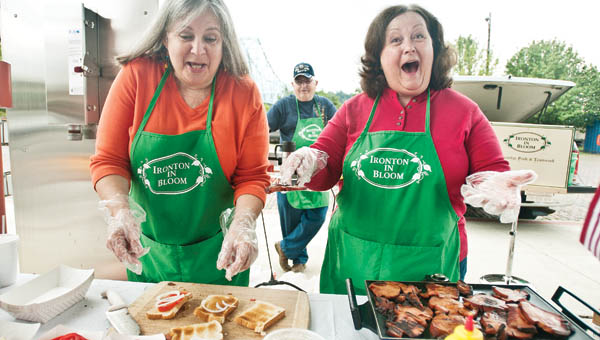 Juanita Dalton, left, and Cindy Caskey, right, serves tomato and bologna sandwiches at the Ironton Farmers Market Saturday in downtown Ironton.