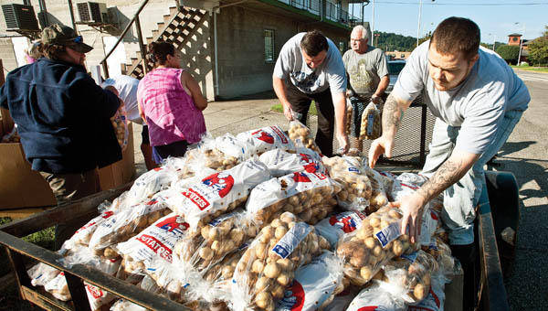 Volunteers with the Harvest for the Hungry food bank in Ironton, help load bags of potatoes into a trailer on Tuesday.