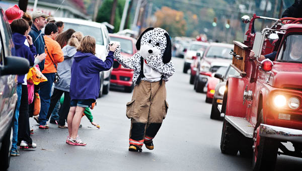 The Chesapeake Firehouse Puppy Dog high fives eventgoers during the annual Chesapeake Octoberfest parade Saturday.