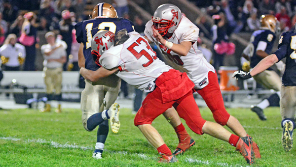 Symmes Valley Vkings' defensive lineman Tyler Dement (53) wraps up Portsmouth Notre Dame running back Michael Collins (12) during Saturday night's game. The Vikings won 34-14 to win a share of the Southern Ohio Conference I football championship. (Kent Sanborn of Southern Ohio Sports Photos)