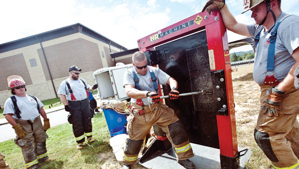 Chris Spears, with the State Fire and Rescue of Kentucky, demonstrates forcible entry techniques during fire school Saturday in South Point.