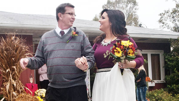 THE TRIBUNE/JESSICA ST JAMES Casey Brislin is escorted by her father, Bob, during a giving-away ceremony.