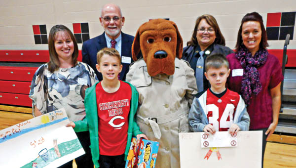 """The Tribune/Brandon Roberts The """"Don't Trash Your Life"""" poster contest winners are, front from left, second-place winner Sam Large, McGruff the Crime Dog, and third-place winner Ashton Smith. First-place winner Carly Robinson is not pictured. Pictured, back row, from left, is Chrystal Pinkerton and Bob Vinson of Spectrum Outreach Services, Julie Jones, Lawrence County deputy sheriff and Stephanie Helms of the Lawrence-Scioto County Solid Waste Management District."""