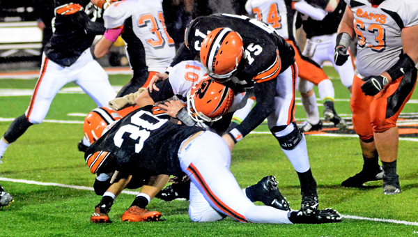 Ironton Fighting Tigers' defenders Isaac Sherman (75) and Andrew Barker (30) combine to bring down Raceland Rams' quarterback Josh Young (10). Ironton beat Raceland 25-12 on Friday. (Kent Sanborn of Southern Ohio Sports Photos)