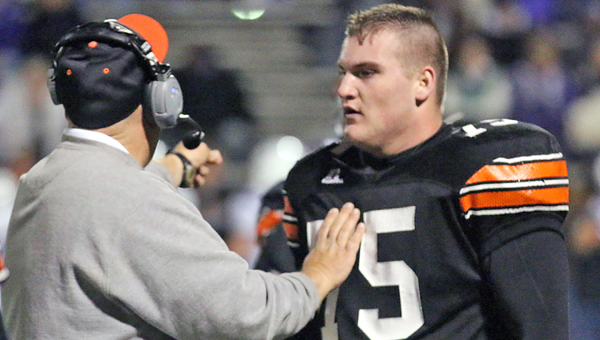 "Ironton Fighting Tigers' senior two-way tackle Isaac Sherman (75) gets some instructions from assistant coach Mike ""Red"" Burcham during Saturday's Division V Region 17 quarterfinal playoff game. Sherman suffered a severe ankle injury in the third quarter of Ironton's 26-13 win over Martins Ferry. Sherman is a three-year starter and the team's best lineman. Ironton plays at 7 p.m. Saturday at Portsmouth in the regional semifinals against Wheelersburg. (Photo Courtesy of Tim Gearhart of Tim's News & Novelties of Ironton)"