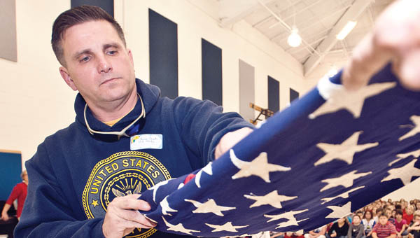 THE TRIBUNE/JESSICA ST JAMES U.S. Navy veteran Bill Crank demonstrates the folding of the flag to students on Monday at Burlington Elementary School during a Veterans Day assembly.