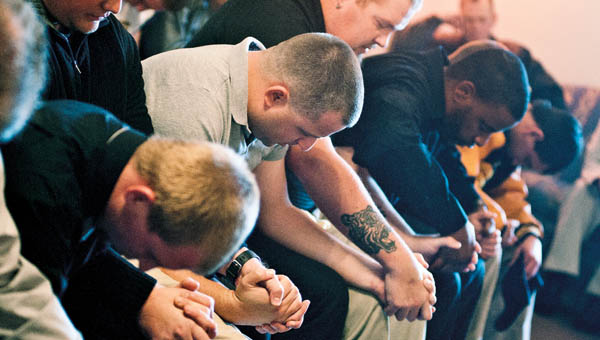 Coaches and team members bow their heads in prayer.