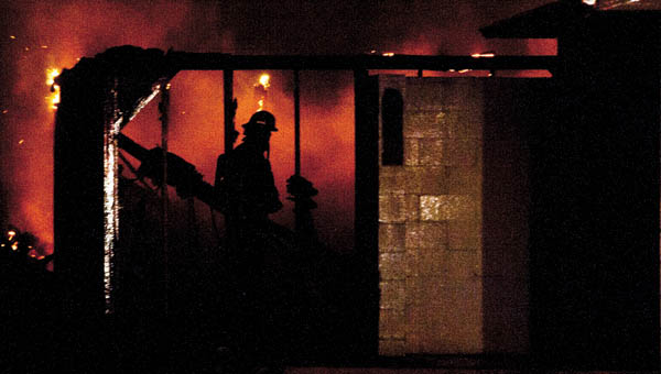 A firefighter from the City of Ironton is silhouetted by the flames of a late night fire on the grounds of the former Fuzzy Duck off of Center Street Tuesday evening.  THE TRIBUNE/JESSICA ST JAMES