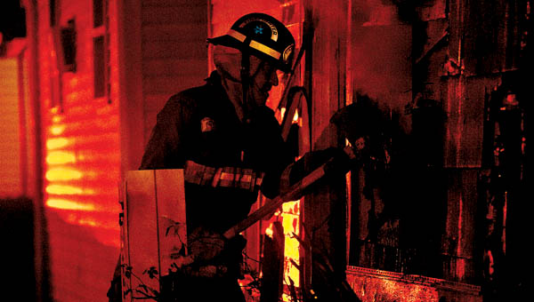 THE TRIBUNE/JESSICA ST JAMES Ironton Fire Fighter Jack Delong uses an ax as he battles a house fire on the 1900 block of South Second Street early Thursday morning. The fire was reported after 5 a.m. and was fully engulfed. The home is a total loss.