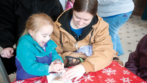 Riley Stapleton, 3 of Kitts Hill, decorates a cookie while her mother, Ashlee Stapleton, looks on.