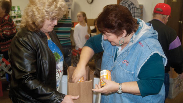 the tribune/michelle goodman Mary Mongold, right, puts canned vegetables in a grocery bag Monday with about 80 other people who helped volunteer to fill food baskets for the Ironton City Mission Church.