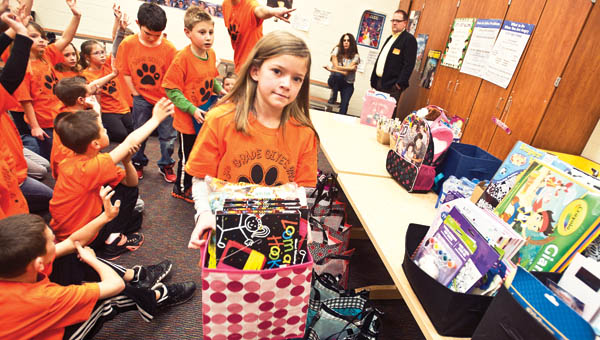 THE TRIBUNE/JESSICA ST JAMES Students from Ironton Elementary School help to load up baskets full of donated items such as toys, games, hairbrushes, books and items for infants to adult teens Thursday.