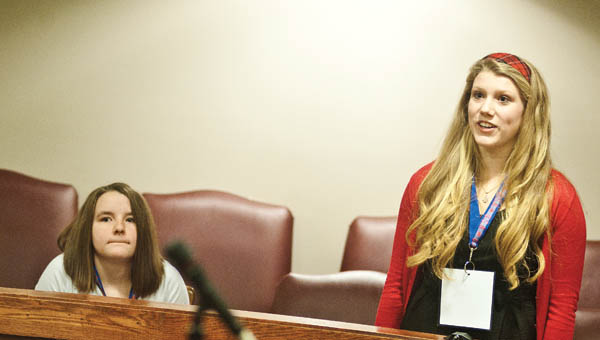 THE TRIBUNE/JESSICA ST JAMES Fairland student Holli Leep begins to show the expression of being a first place winner after spelling the word, popularity, during the 2014 Lawrence County Spelling Bee while Emily Neal watches.