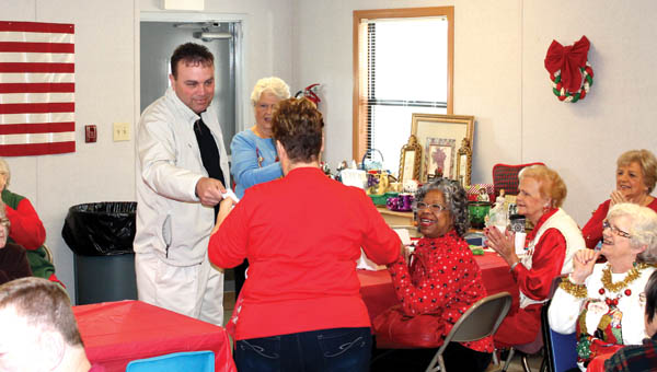 the tribune/dustin melchior Lawrence County Commissioner Freddie Hayes Jr. presents Chesapeake Senior Center director Darlene Green with a check on Monday at the senior center Christmas party and fundraiser.