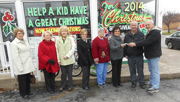 The Tribune/Brandon Roberts The Child Welfare Club presents a check for $265 to co-organizers of the Lawrence County Bicycle Giveaway John Dickess, second from right, and Don Schwartz, far right. The money will be used to buy bikes for the giveaway on Saturday. Pictured, from left, are Child Welfare Club members Janice Haeberlin, Jane Morris, Mary Laber, Sandy Cloran, Madolin Blackwell and Nancy Corn.