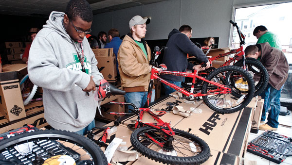 Students from Collins Career Center assemble bicycles Friday.
