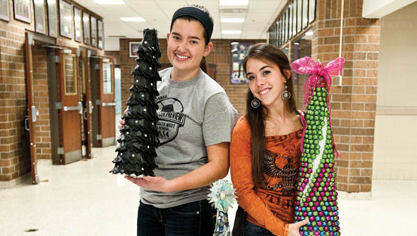 Robin Frye, left, and Laura Rice, right, students at Chesapeake High School show off their Christmas trees.