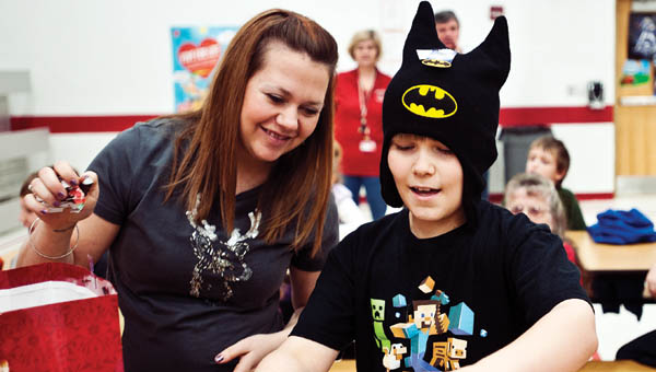 THE TRIBUNE/JESSICA ST JAMES Seven-year-old  Nick Carter dons his new Batman hat while opening a gift with Rebecca Newcomb.