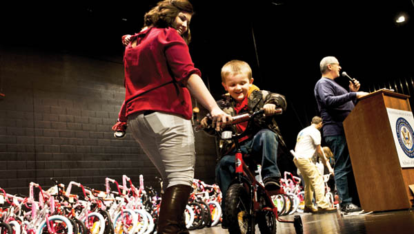 Emily Geswein helps Lycan Chapman after receiving his new bike during the Christmas Bike Giveaway Saturday.