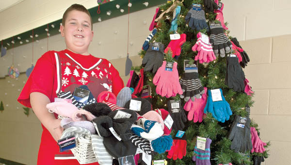 Andrew Medinger, 10, of the Rock Hill Elementary School's fourth-grade class poses next to a hat and mitten tree in the hallway of the school.  THE TRIBUNE/JESSICA ST JAMES