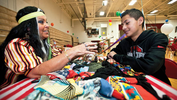 "THE TRIBUNE/JESSICA ST JAMES Rosemary McCarty gives Rock Hill student Victor Aguilera his fortune on Thursday during the ""Carnival of Excellence"" at Rock Hill Middle School."