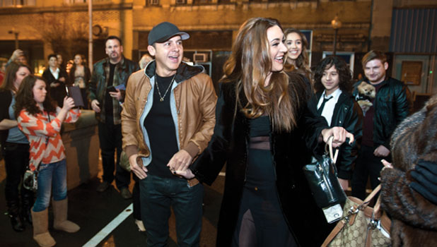 """Gerardo Mejia and his wife Kathy Mejia are welcomed by eventgoers Saturday evening outside the Ro–Na theater for the release party of Mejia's reality show """"Suave Says."""""""