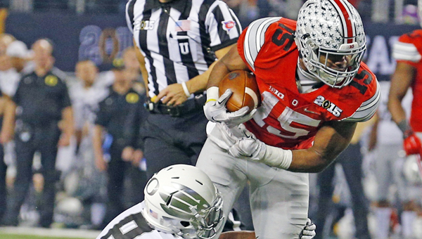 Ohio State Buckeyes running back Ezekiel Elliott (15) is brought down by Oregon Ducks defensive back Reggie Daniels (8) after a third quarter run during the CFP National Championship on Monday at AT&T Stadium in Arlington, Texas. Elliott scored four touchdowns as Ohio State won the national title 42-20. (MCT Direct Photo)