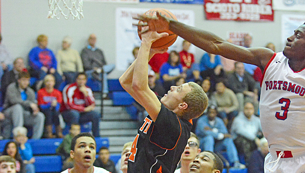 Ironton Fighting Tigers' guard Phillip Kratzenberg (4) drives to the basket against the Portsmouth defense in Friday's game. (Kent Sanborn of Southern Ohio Sports Photos)
