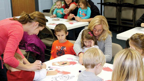 the tribune/dustin melchior (ABOVE) Children work on a Mr. Potato Head craft at the Briggs Lawrence County Public Library in Ironton during the preschool story program on Monday. (BELOW) Michaela Easterling, 3, Sophie Wagner, 6, and Elizabeth Wilson, 4, listen to Jan Gullett tell stories.