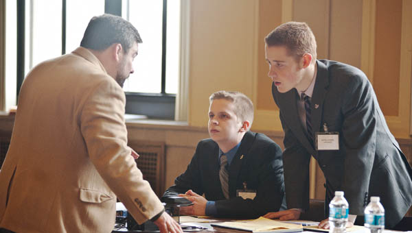 Mock Team Trial legal adviser Mark McCown, left, speaks to St. Joseph High School students Eli Lutz, center, and Daniel Hodges, right, about strategy against undefeated Portsmouth on Friday before the start of the Mock Trial Competition on Friday.