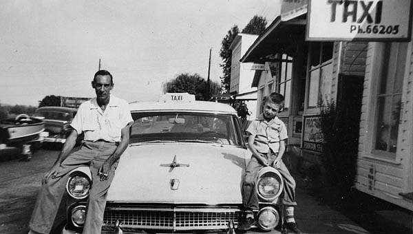 Charles and Tommy Pinkerman sitting on the front of a 1955 Ford taxi in downtown Proctorville. Photo was taken in the summer of 1955.