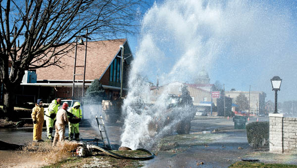 Water gushes as crews work to repair a burst water line on the corner of South Fifth and Washington streets in downtown Ironton.