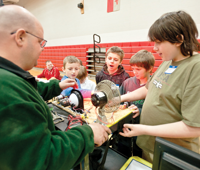 Joe Cook meets with students about electronics and mechanics.