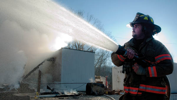 Chesapeake Union firefighter Edgar Moske is semi-silhouetted as he helps to battle an early morning fire at Sky Lake in Windsor Township on Wednesday.