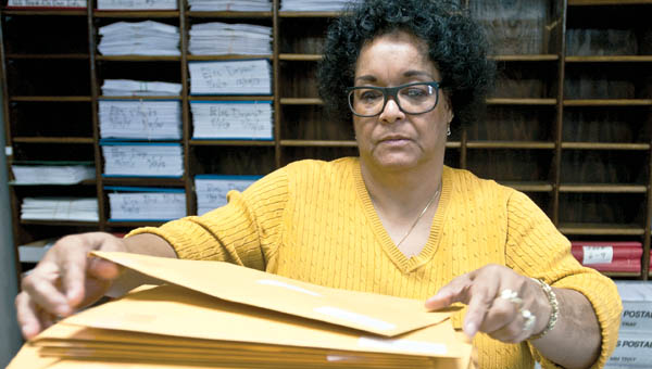 Cynthia Marshall organizes envelops as she and other members in the Lawrence County Treasurer's Office prepare for first half taxes.