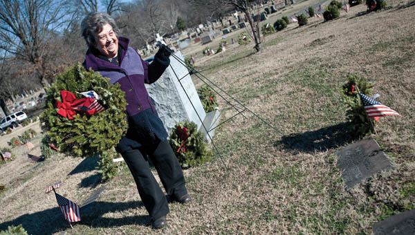 Juanita Southers, Wreaths organizer, removes wreaths from the graves at the soldiers plot at Woodland Cemetery