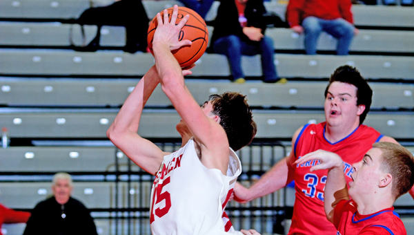 Rock Hill Redmen senior Austin Collins (15) takes a shot despite being tripped on his drive to the basket. Collins scored 20 points but the Redmen lost to Portsmouth 66-46 Saturday. (Kent Sanborn of Southern Ohio Sports Photos)