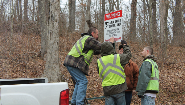 Larry Coleman from the Lawrence Scioto County Solid Waste Management District and community service workers put new signs up in the Wayne National Forest on Friday.