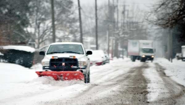Road crews make their way down Pike Street in Coal Grove as they work to clear roads Wednesday.