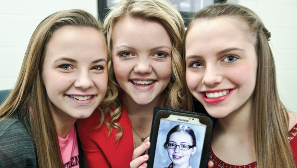 Fairland Middle School students Kelsie Warnock, Emma Conwell and Olivia Roberts, pictured left to right, hold a photo of their friend. Candy passed away from cancer back in July. Today the girls and their fellow students will present a check for $2,000 in honor of Candy to Hospice of Huntington.