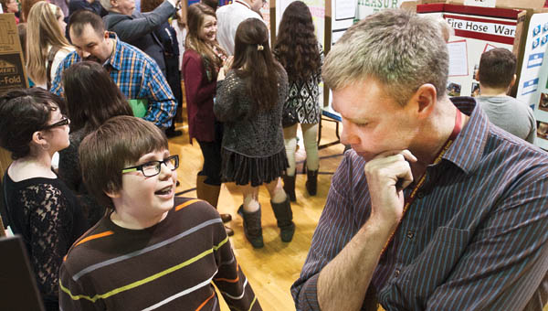 """South Point school student Sean Hackney discusses his project """"Under Siege"""" to judge Patrick Leighty during the 2015 Lawrence County Science Fair."""