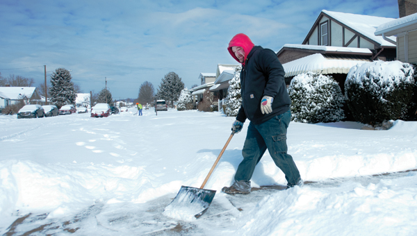 Ironton resident Todd York spends the late morning shoveling snow off the sidewalks around his home Tuesday.