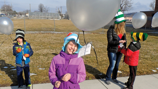 Brooke Ridenour, center, with William McComas, left, and aide Rachel Petitt and David Cooper, right, hold onto their balloons before the launch this past Monday.