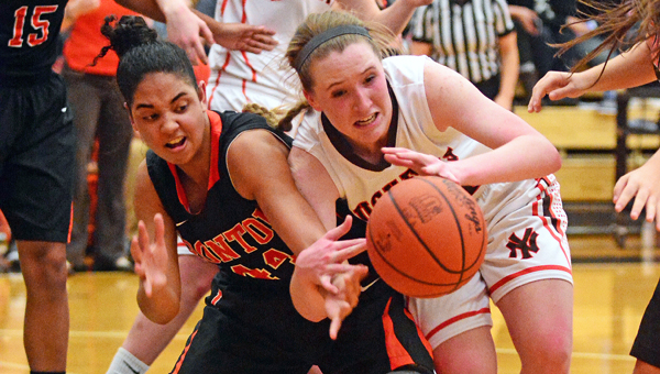 Ironton Lady Fighting Tigers' Cheyenne Scott (left) battles Nelsonville-York Kaitlyn Hurd for a loose ball. Ironton plays Fort Frye and Fairland plays Wheelersburg in the Division III regional tournament Wednesday at Logan. (Kent Sanborn of Southern Ohio Sports Photos)