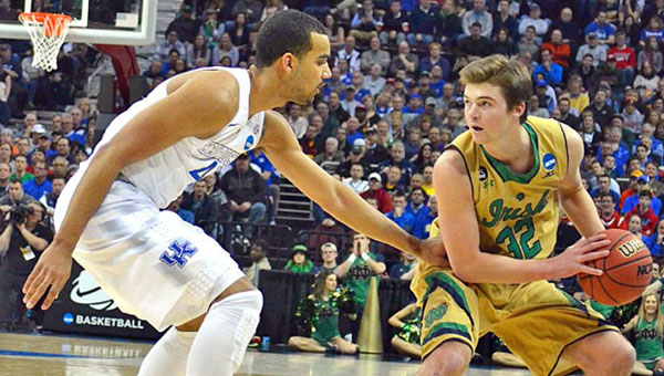 Notre Dame Fighting Irish guard Steve Vasturia (32) is guarded by Kentucky Wildcats' Trey Lyles during Saturday's NCAA Division I regional championship game. The No.1-ranked Wildcats rallied to escape with a 68-66 win. (Photo Courtesy Mike Caldwell/Publisher & President Leader Publications)