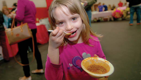 Six-year-old Abby Cox, of Greenup, enjoys her chili as she and her family make the rounds during the Chili Fest and Craft Show for DD Awareness Saturday at Dawson-Bryant High School.